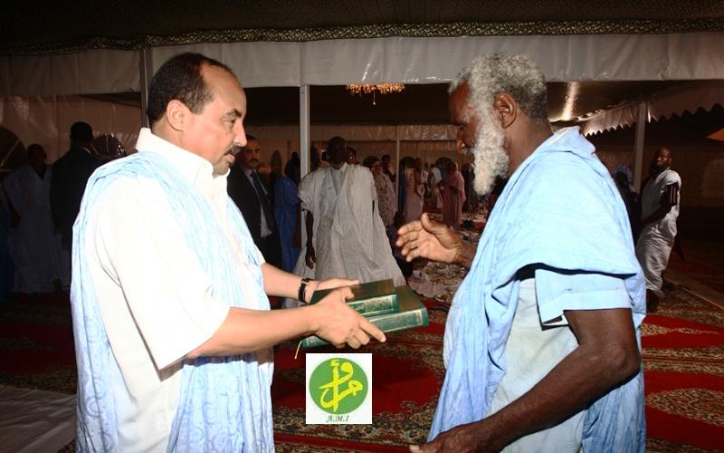 الرئيس الموريتاني محمد ولد عبد العزيز يقدم نسخة من المصحف الموريتاني لأحد سكان الأحياء الفقرة بنواكشوط (وما)